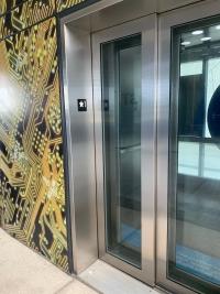 Puerta del ascensor de vidrio y con señalética a la salida